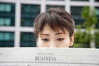 A woman attentively reading the newspaper