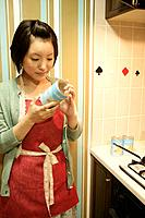A young woman at kitchen, getting ready to cook