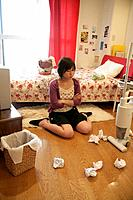 A young woman sitting in front of bits of papers and a dustbin inside a messy room