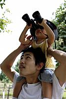 A boy on father´s shoulder, looking into binoculars