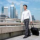 Low angle view of a businessman pulling a suitcase