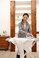 View of a young woman ironing a shirt