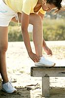 A young woman ties her shoe lace as she keeps her foot on the wooden table