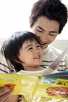 A young father reading a book to his son