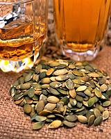 Closed Up Image of Several Pumpkin Seeds Next to Two Glasses of Beer, High Angle View, Differential Focus