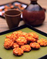 Closed Up Image of a Japanese Snack, Several Fried Rice Crackers Next to Some Tea, High Angle View, Differential Focus