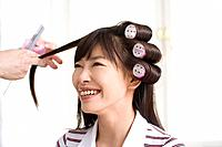 Hairdresser cutting putting curlers in young woman's hair