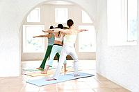 Young women doing yoga exercise, stretching, rear view