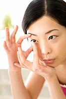 Young Woman inserting contact lens, Close Up, Front View (thumbnail)
