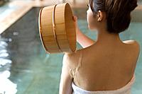 Woman pouring water on her shoulder with wooden tub, rear view, Japan (thumbnail)