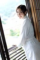 Portrait of a woman in bathrobe by the window, smiling and looking at camera, side view, Japan