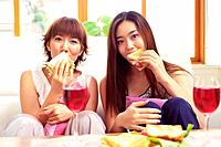 Two Young Adult Women Eating Sandwiches and Drinking Red Wine, Looking at Camera, Front View