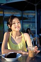 Young Lady Sitting at Outdoor Cafe, Looking Away