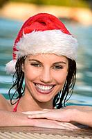 Asia, Thailand, ´Young woman wearing Santa Claus cap, smiling, portrait