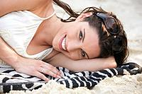 Asia, Thailand, Young woman lying on beach, smiling, portrait