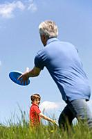 Germany, Baden Württemberg, Tübingen, Grandfahter and grandson playing frisbee