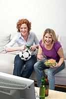 Two friends watching TV with football, beer and salad