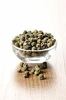 Green peppercorns in a small glass dish
