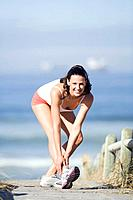 Young woman stretching leg, smiling, portrait