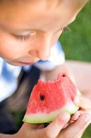 Small boy eating a piece of watermelon