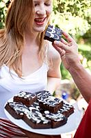 Man´s hand offering woman a brownie at a garden party