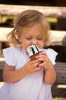 Small girl eating a chocolate ice cream cone