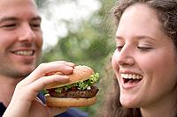 Man offering woman a bite of hamburger