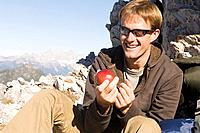 Austria, Salzburg County, Young man holding an apple