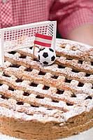 Woman holding Linzer torte with football, goal & Austrian flag