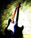 blue and white guitar leaned against wall