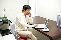 Mid adult man talking on mobile phone and laptop computer in front of the desk