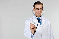 Young doctor holding stethoscope, portrait
