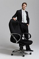 Businessperson standing beside chair, portrait