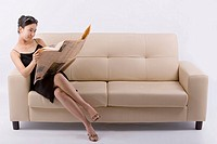 Businesswoman sitting on sofa, reading magazine