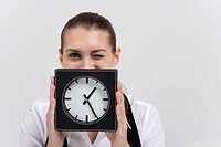 Portrait of young businesswoman holding clock, winking