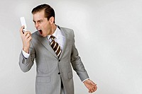Businessman shouting looking at mobile phone, close_up