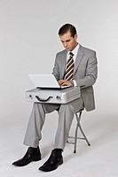 Businessperson sitting on chair working on laptop
