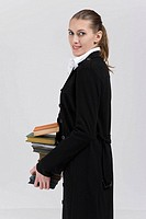 Young businesswoman holding stack of books, portrait