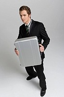 Young businessman holding briefcase, portrait