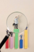 View of figurine through magnifying glass standing on bar chart