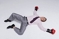 Businessman lying down wearing boxing gloves