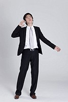 Young businessman listening to music, wearing headphones