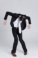 Portrait of young businessman listening to music, dancing, wearing headphones