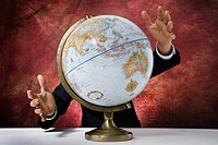Mid section view of a businessman standing behind a globe