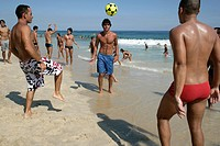 Men playing football on Ipanema beach, Rio de Janeiro, Brazil