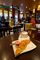 Croissant and coffee laid out for breakfast in a cafe , Paris, France