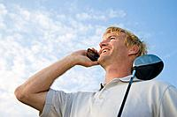 Man holding golf club, speaking on cell phone