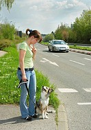 australian sheperd puppy and woman _ standing at street / restrictions: Tierratgeber_Bücher / animal guidebooks