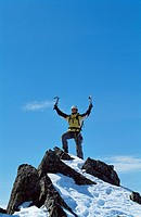 Mountain climber standing on snowy mountain victorious and smiling