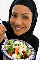 Woman holding bowl of salad and smiling studio shot/selective focus